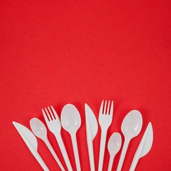Композиция из белых пластиковых столовых приборов на ярко-красном фоне