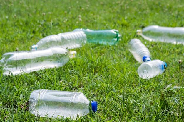 屋外で緑の芝生の上の廃プラスチック水のボトル