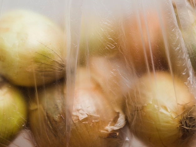Крупный план органического лука в полиэтиленовом пакете