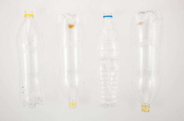 白い表面上のリサイクルのための空のペットボトルの行