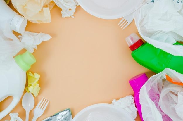 ベージュ色の背景上のプラスチック製ゴミのオーバーヘッドビュー