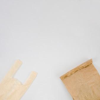 Пластиковый пакет и коричневый бумажный пакет с копией пространства на белом фоне