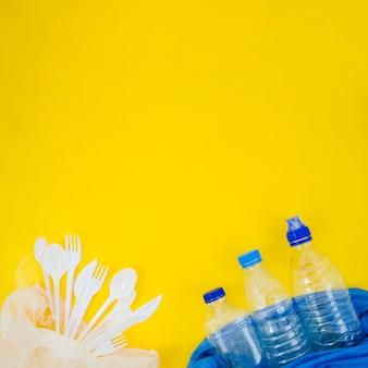 プラスチック製のフォークとスプーンで黄色の背景上のビニール袋に空のペットボトル