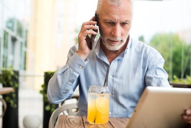 正面の老人が電話で話しています。