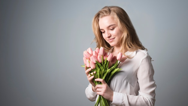 Очаровательная блондинка наслаждается букетом цветов