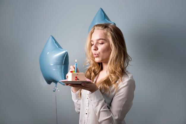 夢のような若い女性がケーキの上のろうそくを吹き