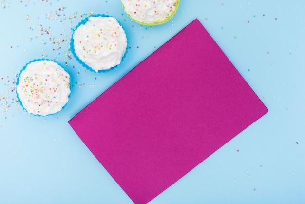 空のピンクのカードとカラフルなカップケーキ