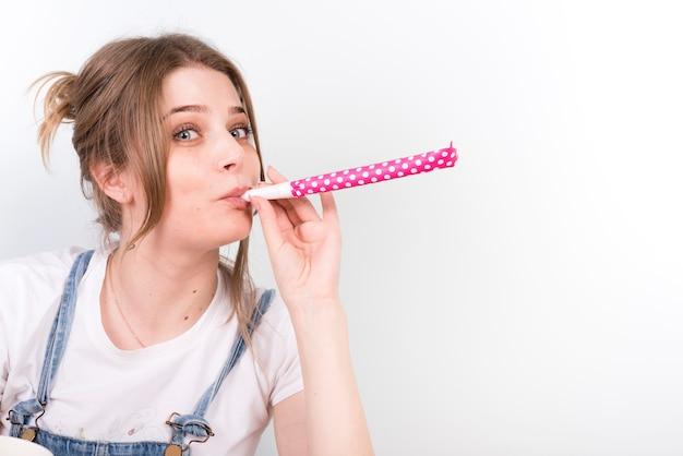 鳴り物を吹いているカジュアルな若い女性