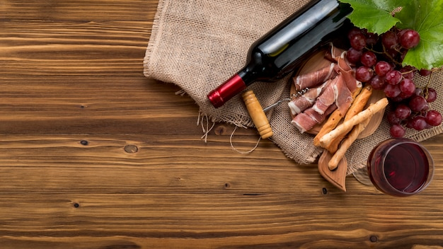 Вид сверху вино с едой и гроздью винограда