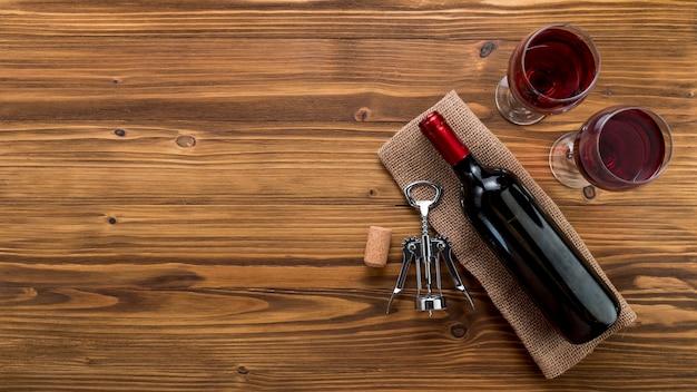 木製の背景上のガラスとトップビューワインボトル