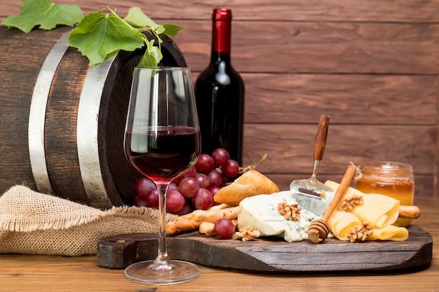 Деревянная бочка рядом с вином и тапой