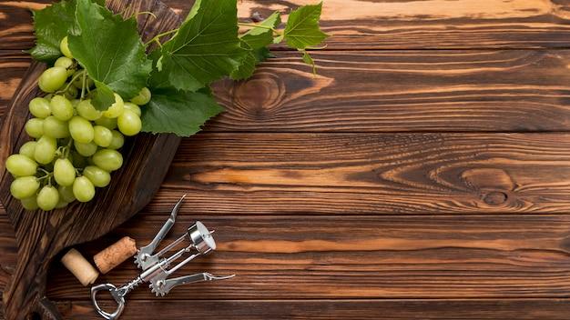 木製の背景にコルク栓抜きとブドウの房