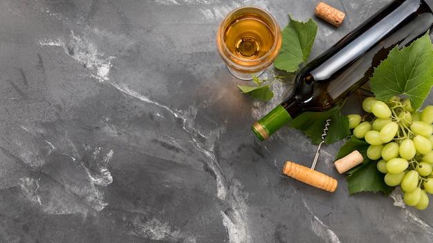 大理石の背景にワインのボトルとブドウの房