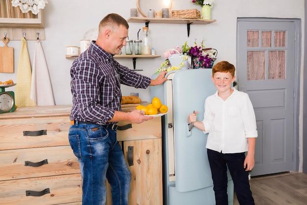 父と息子は台所でポーズをとる
