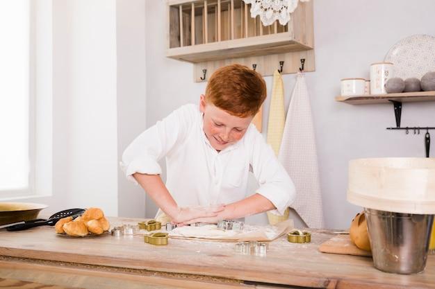 台所でレシピを準備する少年
