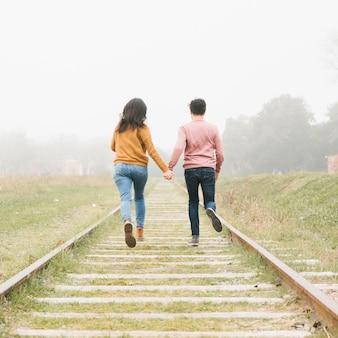 Молодая пара бежит по дорожкам