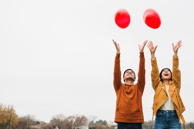 遊び心のある若いカップルが風船を手放す