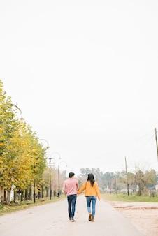若いカップルが道に沿って散歩