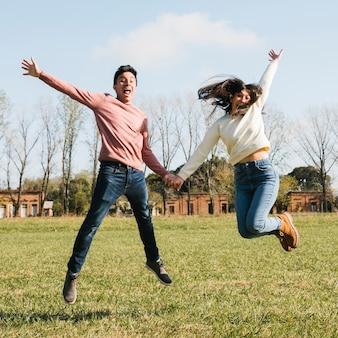 幸せな若いカップルジャンプ