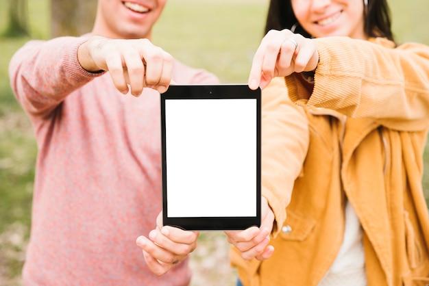 陽気なカップルのタブレットで立っています。
