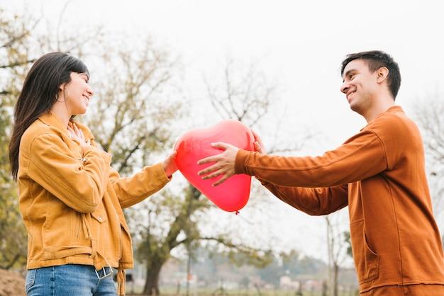 ハート型のバルーンを保持している若いカップル