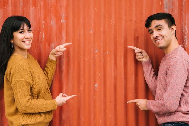 オレンジ色のフェンスを指している若いカップル