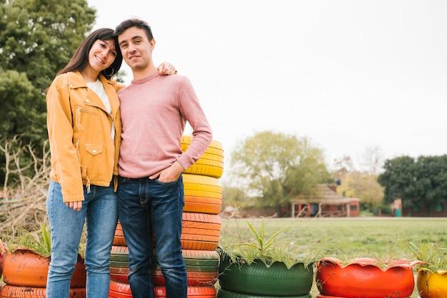 Молодая оптимистичная пара обнимаются в осеннем парке
