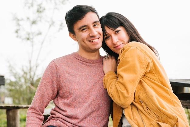 笑顔のカップルを抱きしめるとカメラ目線