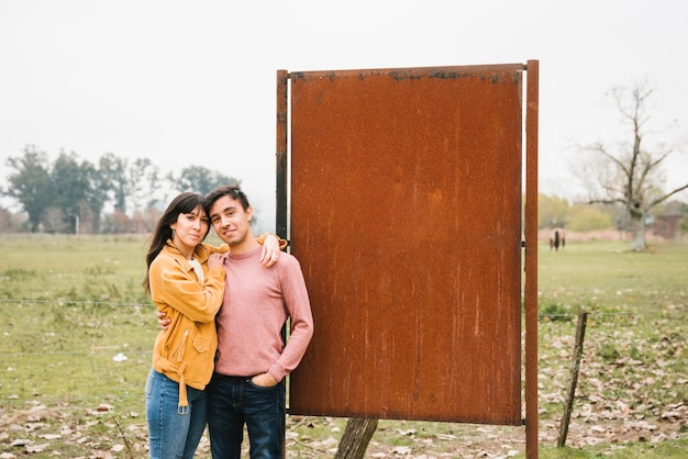 Улыбающиеся пара обнимаются в осеннем парке рядом с металлической ржавой подставкой