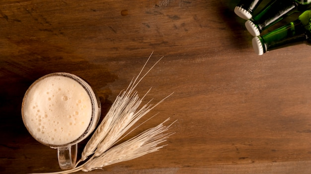 小麦の穂と木製のテーブルの上の緑の瓶とビールのグラス