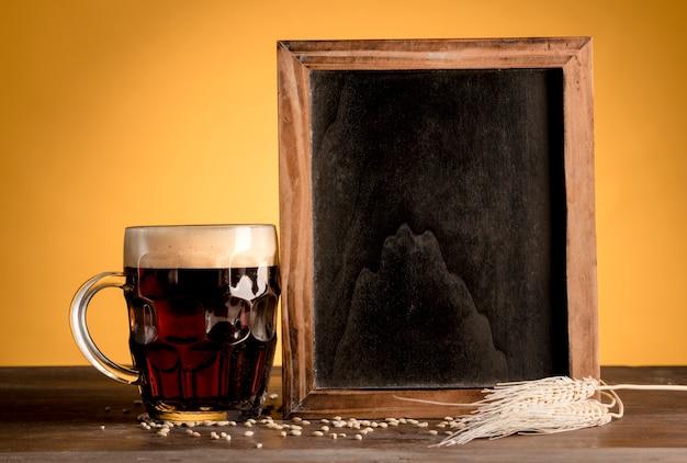 黒板に立っている次の木製のテーブルの上のビールのグラス