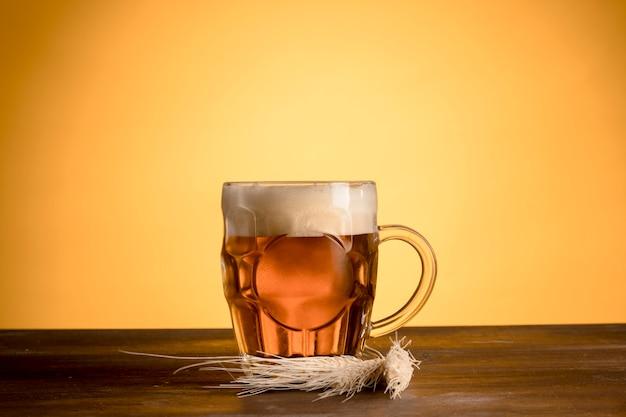 木製テーブルの上の大麦スパイクと軽いビールのグラス