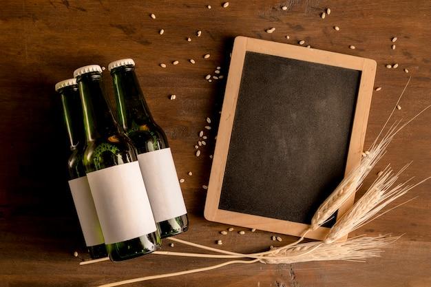 木製のテーブルに黒板とビールの緑色の瓶のモックアップ
