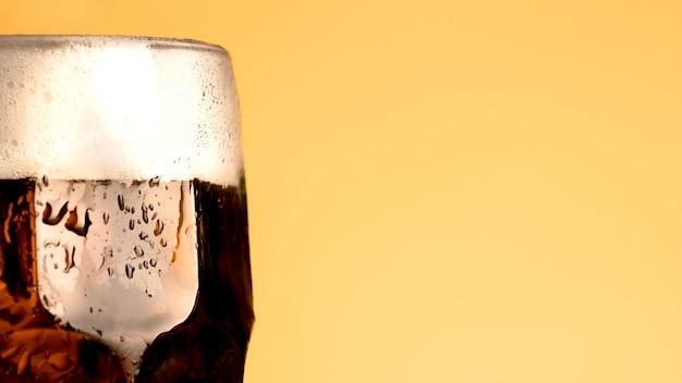 黄色の背景にビールの冷たいガラス