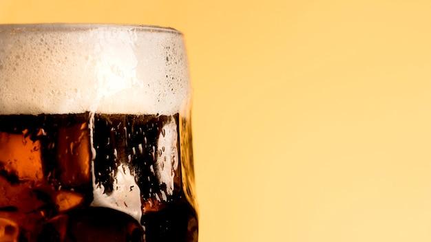 オレンジ色の背景上のビールの新鮮なガラス