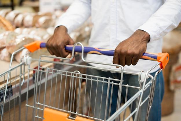 Черный мужчина выбирая хлеб в продуктовом магазине