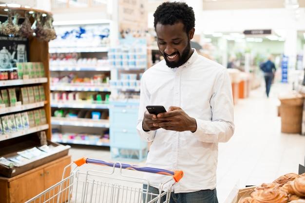 Веселый черный человек, набрав на мобильном телефоне в продуктовом магазине