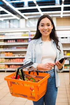 陽気なアジア女性の買い物かごを市場で運ぶ
