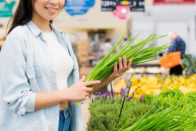 食料品店で緑を選ぶ女性の笑みを浮かべてください。