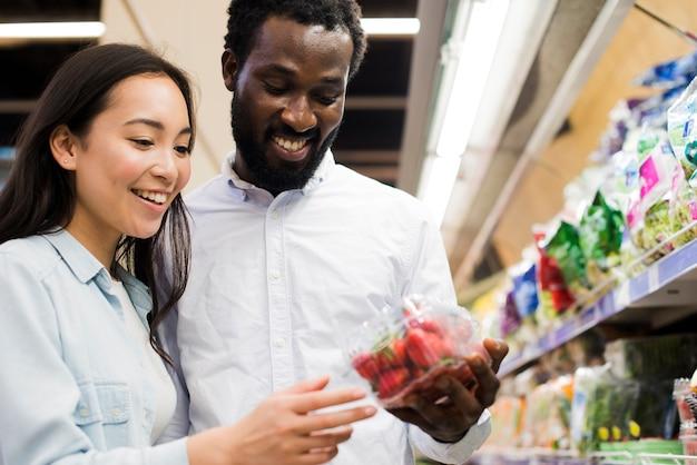 陽気なカップルが食料品店でイチゴを選ぶ