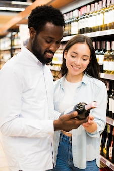 陽気なカップルが食料品店でワインを選ぶ