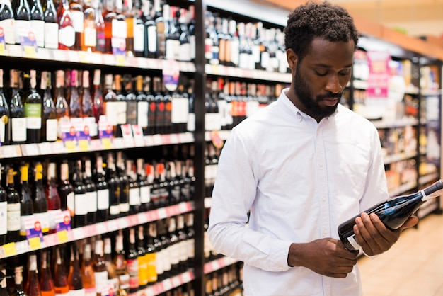 Человек, выбирая бутылку вина в разделе алкоголя