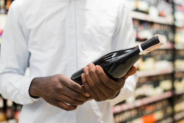 Мужчина осматривает бутылку вина в секции алкоголя