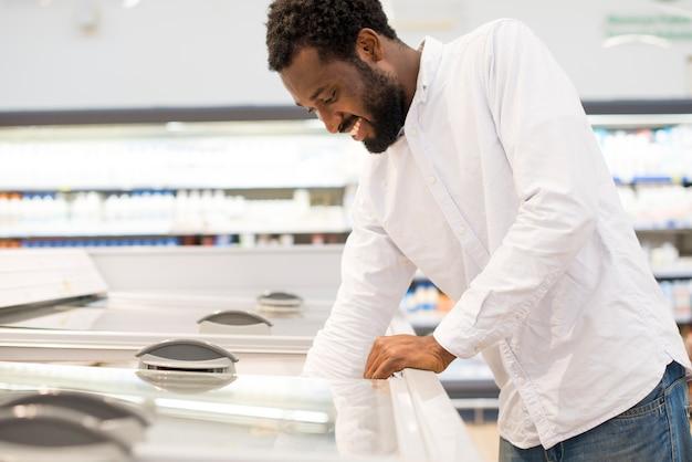 Человек протягивает руку в супермаркет морозильник