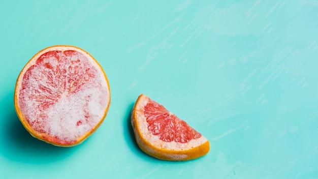 ターコイズブルーの背景に冷凍グレープフルーツ