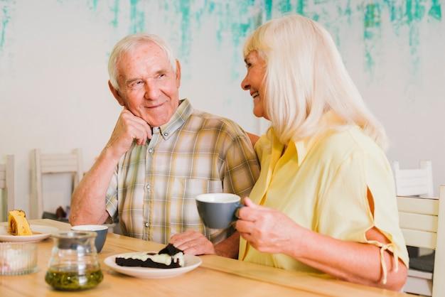 Веселая пожилая пара пьет чай и разговаривает