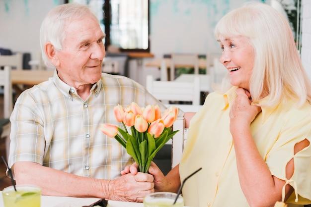 Пожилой мужчина дарит цветы любимой