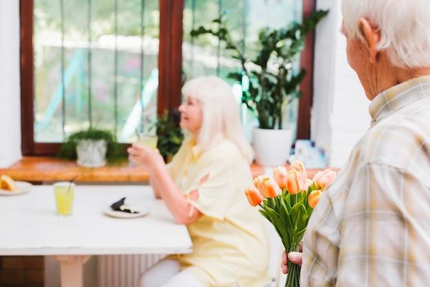 Пожилой мужчина собирается дарить цветы любимой