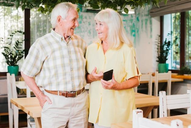 Пожилая женщина делит смартфон с мужем