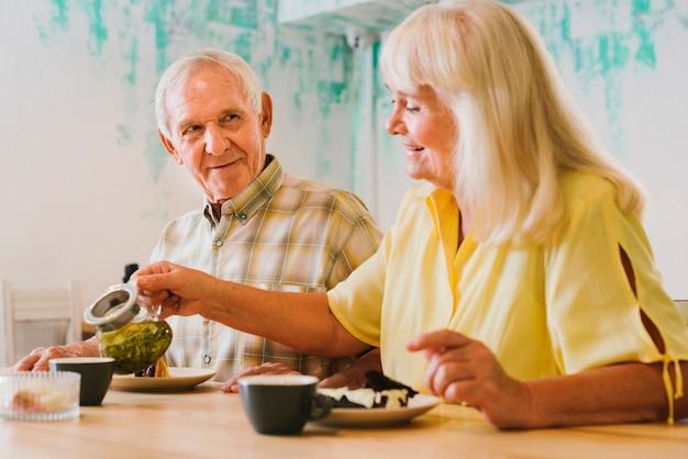 灰色の髪の男にお茶を注ぐ高齢者の女性